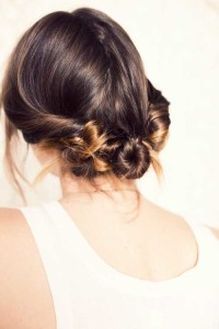 Medium, dark brown hair with tied locks and a bun