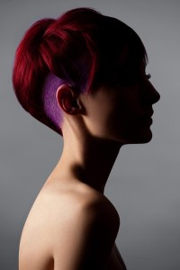 Short, red, cropped hair with shaved and purple coloured sides