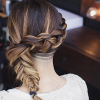 Long, brown hair with a thick french braid and a shaved back