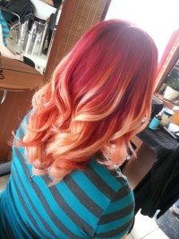 An amazing ombre effect on red, curly hair with yellow highlights
