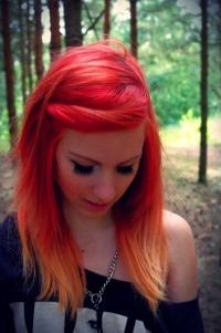 A cute hairstyle for red headed girls with yellow and orange endings and tied locks