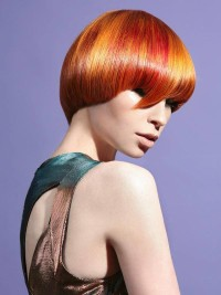 Short, cropped, red hairstyle with regular cutting, brow skimming bangs and yellow highlights