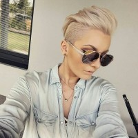 Short, blonde haircut with long, spiky bangs and shaved sides