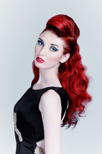 Pin-up stylization with long and curly, red, tied hair and comb fringe