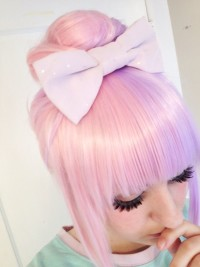 Cute, long, powder pink hairstyle with blunt bangs and tied hair in a bun, decorated with a bow