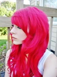 Long, heavy, neon pink hairstyle with side-swept bangs