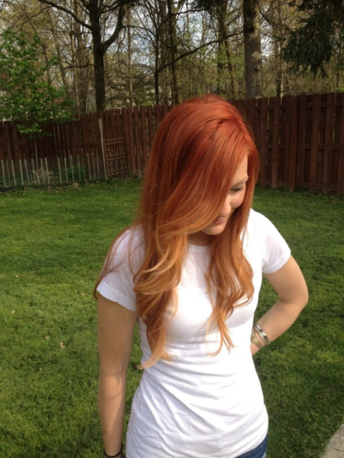 Long, red ombre looking hairstyle with side-swept fringe and curls