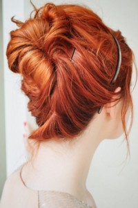 Long, copper hair tied in a bun and decorated with hair band