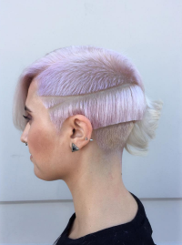 Short, platinum hairstyle with powder pink highlights, trimmed side layers and long fringe