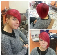 Short, red hairstyle with shaved, dark sides and long, red finge