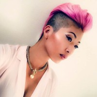 Short, extravagant hairstyle with pink combed fringe and shaved sides