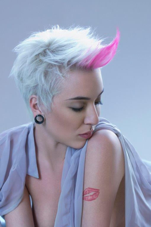 Short, platinum hairstyle with spiky pink layers of fringe