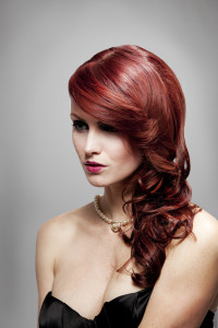 Long, red hair hairstyle with curly endings and side-swept bangs