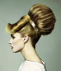 Amazing hairstyle with big bun tied with a band and side-rolled bangs
