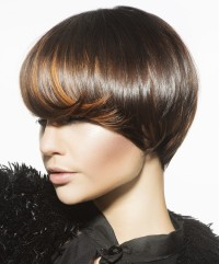 Short, brown hairstyle with blonde highlights