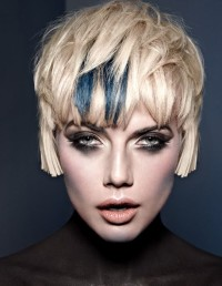 Short, choppy, pixie hairstyle with blue highlights and regular cutted backs