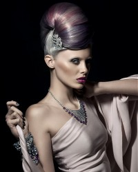 An updo with high, violet bun and short, platinum backs
