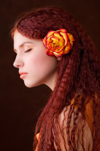 Long, crimped, red hairstyle with rose in hair