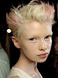 Short, spiky hairstyle with pink highlights