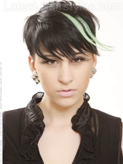 Short, black haircut with wispy bangs and green highlights