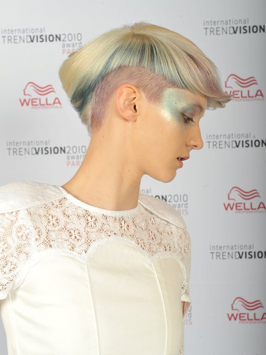 Short, bowl cut hairstyle with shaved sides and green highlights