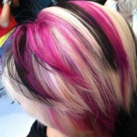 Medium-length, layered hairstyle with black, pink and blonde highlights