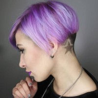 Short, pixie hairstyle with violet reflections and star shaved sign