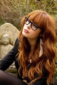 Long, wavy, red hairstyle with blunt bangs