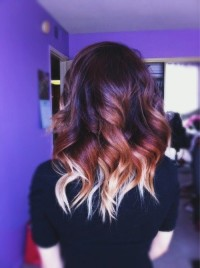 Long, dark hairstyle with curls and blonde endings