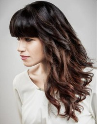 Long, wavy, dark hairstyle with blunt bangs and curls